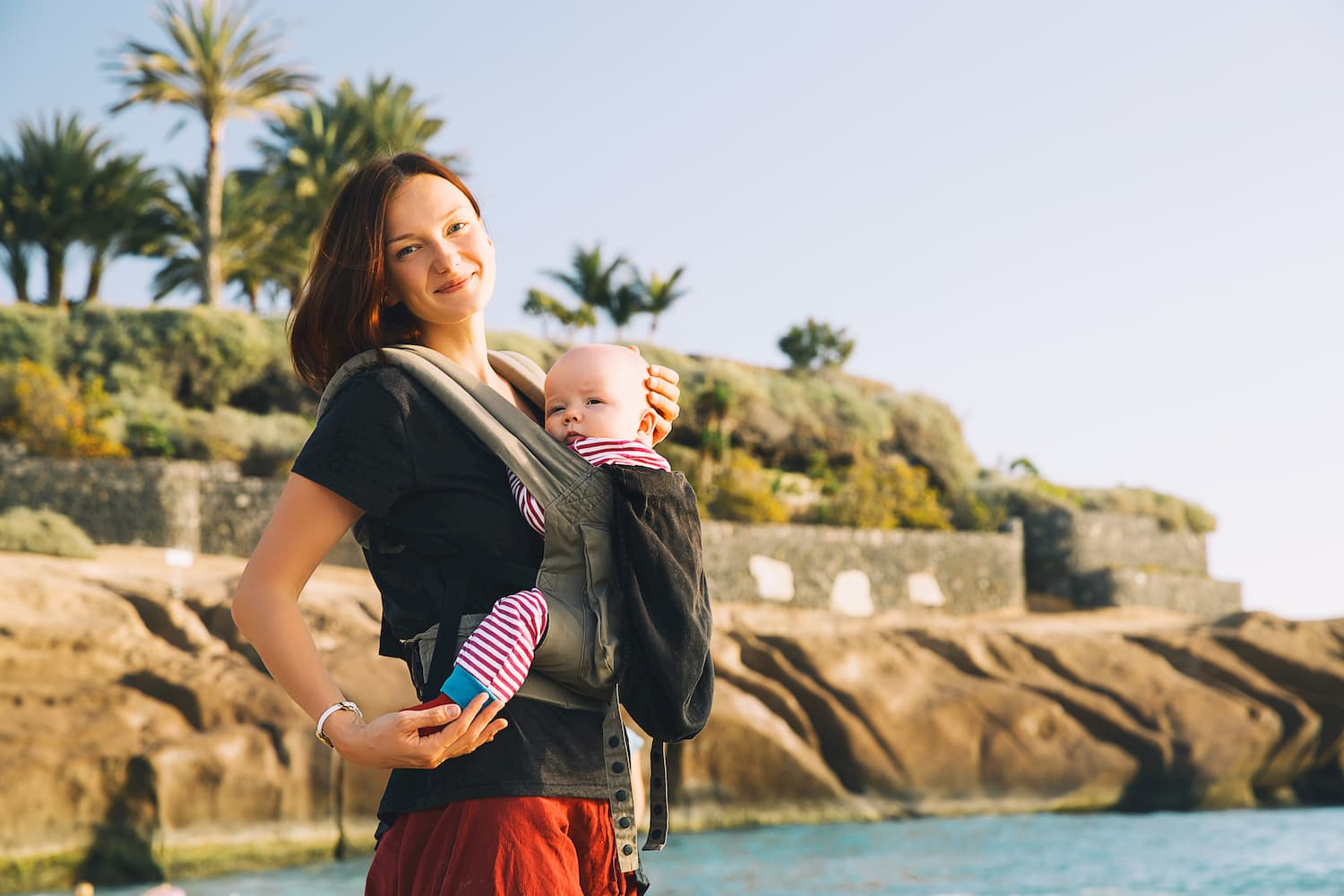 Mother with a baby in a baby carrier on the coast of ocean