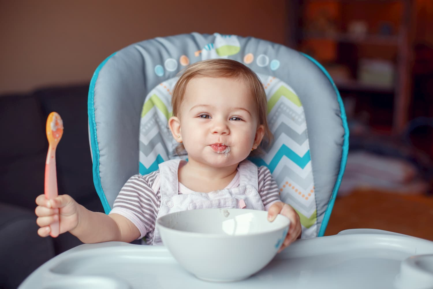 High Chair With a Baby Girl Who Eats Cereal